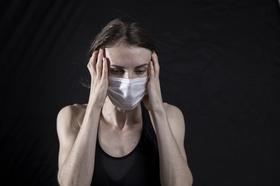 Frau mit Maske und Kopfweh