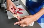 Frau mit Schnittwunde am Finger schneidet sich Pflaster zurecht
