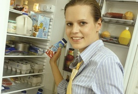 Frau nimmt Essen aus Kühlschrank