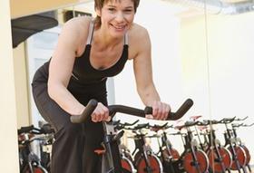 Frau in Fitnessstudio auf Ergometer