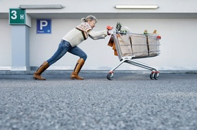 Frau schiebt angestrengt einen vollen Einkaufswagen