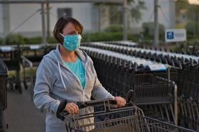 Frau schiebt Einkaufswagen mit Mundschutz