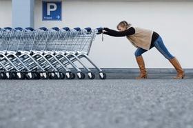Frau schiebt Reihe von leeren Einkaufswagen