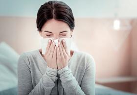 Frau schnäuzt sich die Nase (1)