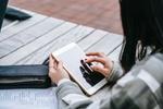 Frau scrollt beim Lernen über Smartphone