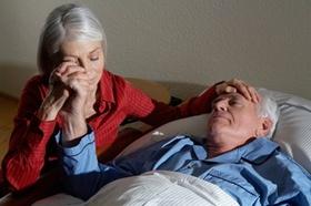 Frau sitzt am Bett eines alten Mannes und hält seine Hand
