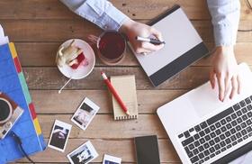 Frau sitzt an modernem Arbeitsplatz mit Tee und Fotos