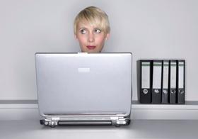 Frau sitzt an Tisch hinter Notebook