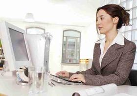 Frau sitzt im Buero am Computer