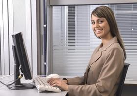 Frau sitzt im Büro an Computer