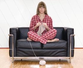 Frau sitzt im Pyjama im Schneidersitz auf Sofa und strickt