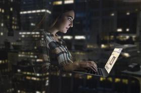 Frau sitzt in der Nacht im Bürogebäude und tippt am Laptop