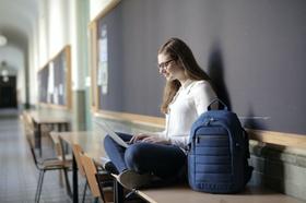Frau sitzt in Schulflur und tippt in einen Laptop
