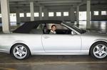 Frau sitzt in silberfarbenem Cabriolet im Parkhaus