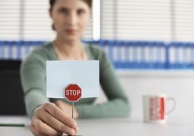 Frau sitzt mit kleinem Stoppschild an Schreibtisch