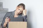 Frau sitzt traurig nach Kündigung mit ihren Sachen auf Treppe