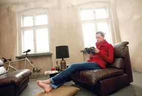 Frau sitzt zuhause in altem Ledersessel, liest