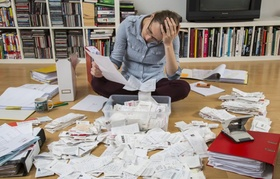 Frau sortiert Belege, Unterlagen, Rechnungen und Kassenbons auf dem Boden, für die Steuererklärung
