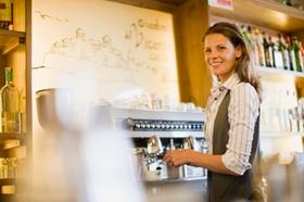 Frau steht hinter der Theke an Profi-Espressomaschine und schaut über die Schulter in die Kamera