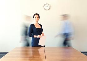 Frau steht im Büro an Konferenztisch, zwei Kollegen in Bewegung