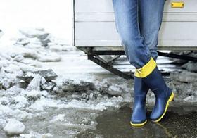 Frau steht mit Gummistiefeln im Schneematsch, Detail Beine