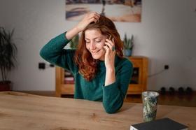Frau telefoniert am Esstisch