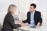 Frau und Mann in Business Kleidung sitzen am Tisch und diskutieren