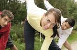 Frau und zwei Maenner bei Gymnastik im Freien