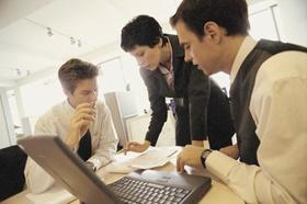 Frau und zwei Männer um Laptop mit Unterlagen