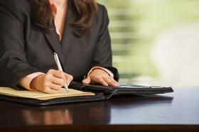 Frau unterschreibt Vertrag oder notiert sich etwas