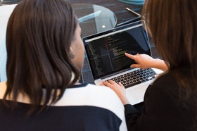 Frau zeigt mit Zeigefinger einer anderen Frau etwas auf dem Laptop