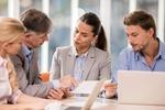 Frau zeigt Mann in einem Meeting ein Schriftstück
