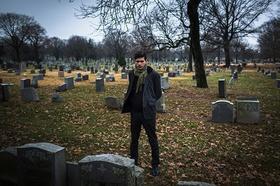 Friedhof mit Mann der auf einen Grabstein blickt
