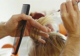 Friseur schneidet Haare, Detail Haende