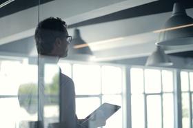 Führungskräft hält hinter Glas ein Tablet in der Hand
