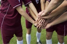 Fußballspieler legen die Hände aufeinander, fully_released