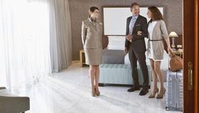 Gäste und Mitarbeiterin in einem Hotel-Zimmer