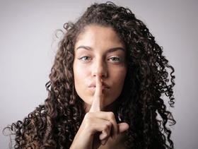 Geheimnis: Frau hält sich Finger vor den Mund