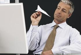 Gelangweilter Mann mit Papierflieger