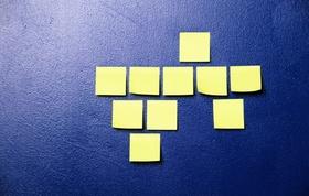 Gelbe Post-it Zettel kleben an blauer Wand