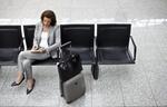 Geschäftsfrau macht Notizen am Flughafen mit Gepäck