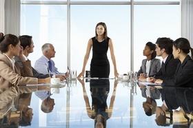 Geschäftsfrau steht an Meetingtisch und spricht in die Runde