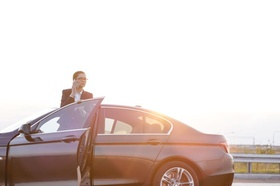 Geschäftsfrau steigt telefonierend aus Dienstwagen