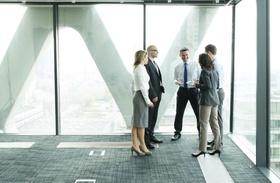 Geschäftsleute besprechen sich fröhlich in hellem Büro