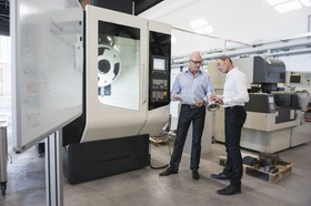 Geschäftsmänner kontrollieren große Maschine in Fabrik