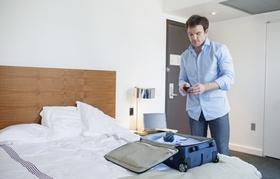 Geschäftsmann beim Koffer Packen im Hotelzimmer