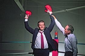 Geschäftsmann der Boxhandschuhe in Siegergeste hochhält