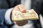 Geschäftsmann hält Bündel Geldscheine in die Kamera