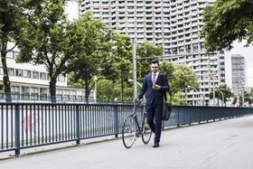 Geschäftsmann läuft mit Fahrrad an Brücke entlang und guckt auf sein smart phone