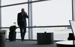 Geschäftsmann mit Gepäck telefoniert am Flughafen